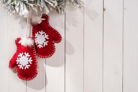 木材の背景とテキストのための場所のミトンの形のモミの枝とのクリスマスの装飾