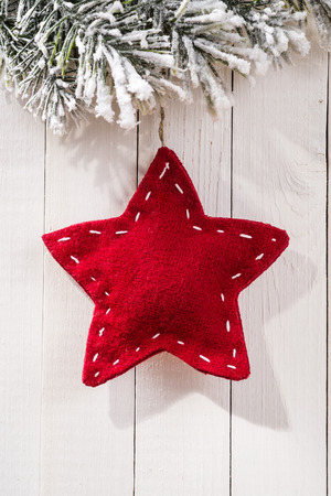 Christmas decoration with fir branches in the shape of a star on wood background