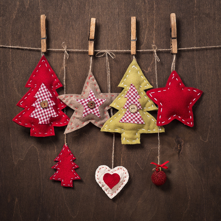 Christmas decorations on a background of wood. Crafts made of felt made by hand Reklamní fotografie