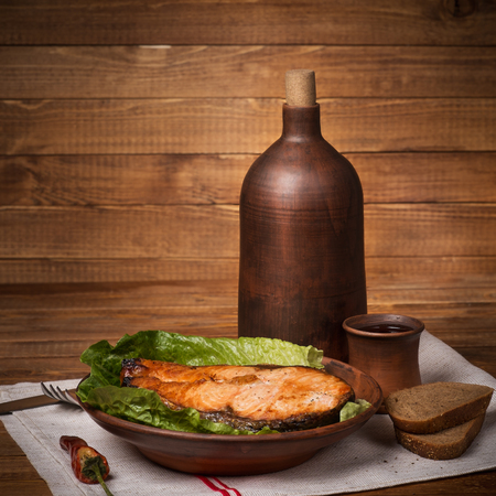 Still life in a rustic style baked trout and a jug of wine photo