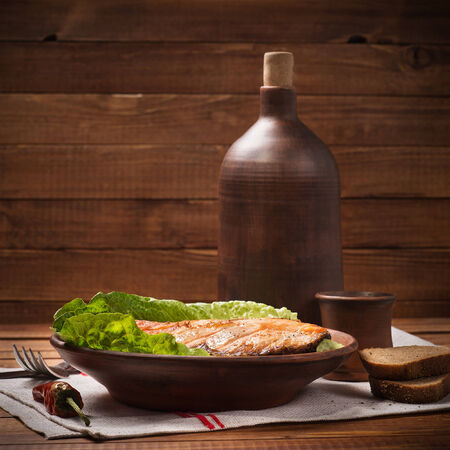 Baked trout in a clay plate photo
