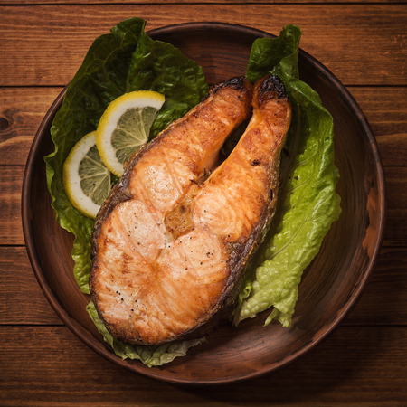 Baked trout steak in pottery with salad and slices of lemon, top view