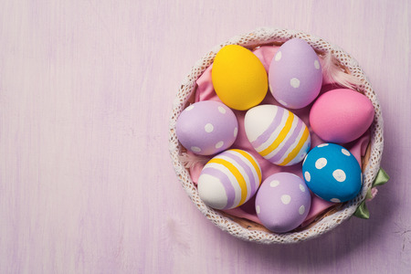 Colorful Easter eggs in a basket, with space for text. Top view