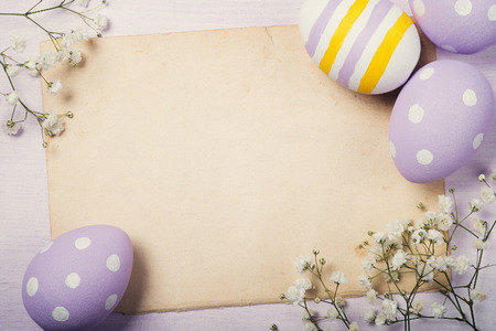 Colorful Easter eggs and flowers on old sheet of paper with space for text. Top view Stock Photo