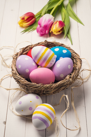 Fresh tulips and colorful easter eggs in a nest on a wooden table photo