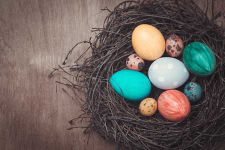 holiday tradition: Colorful Easter eggs in a nest in a rustic style and place for text