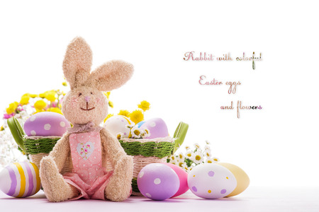 Soft toy in the shape of a rabbit with colorful Easter eggs and flowers. Space for text. Stock Photo