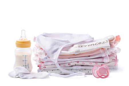 fondo para bebe: Ropa doblada para beb�s con una botella de leche y chupete sobre un fondo blanco Foto de archivo