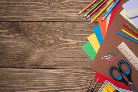 School supplies on a wooden table with space for text, top view Imagens
