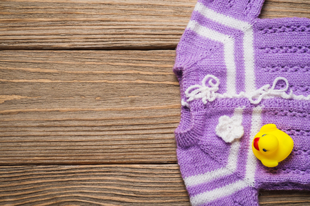 knitted jacket: Knitted jacket for the baby on a wooden table with space for text, top view
