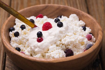 sour cream: Cottage cheese with sour cream, ripe blueberries and currants, closeup