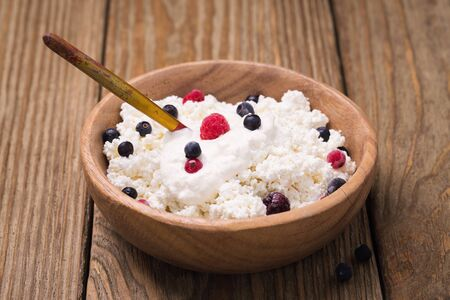 sour cream: Cottage cheese with sour cream and frozen berries Stock Photo