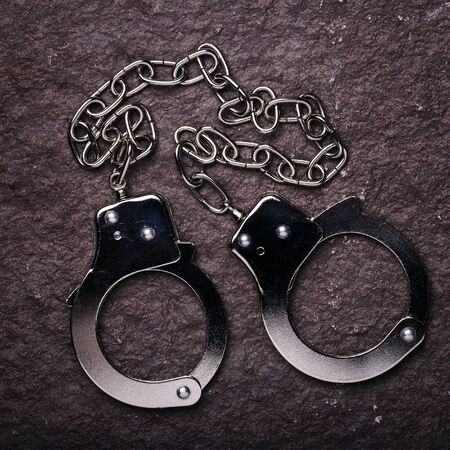 metal handcuffs: Metal handcuffs on the stone surface, top view Stock Photo