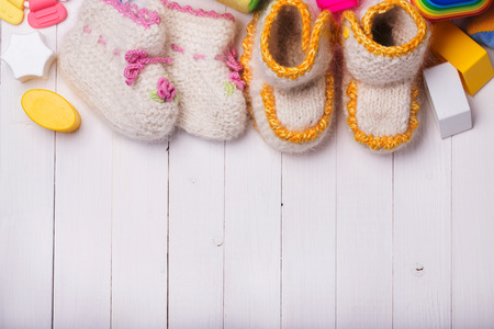 backcloth: Booties for babies handmade surrounded by toys with space for text