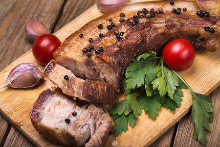 Roast pork belly with spices on a wooden board, close-up