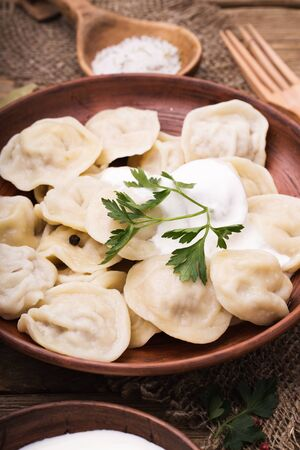 sour cream: Homemade meat dumplings with sour cream and parsley close-up