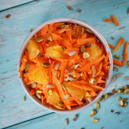 Carrot salad with orange sauce, pistachio nuts and seeds, top view