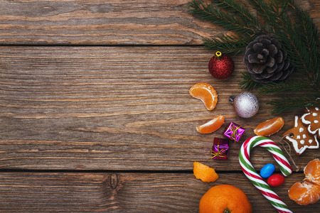 Christmas decorations on the right side on a wooden background with space for text, top view