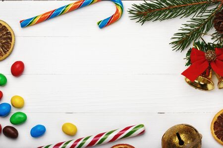 Frame of sweets and other Christmas items on white background