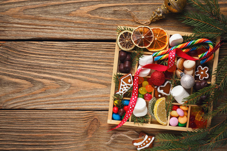 Cookies, candy, marshmallow and marmalade in a wooden box with space for text, top view Stock Photo