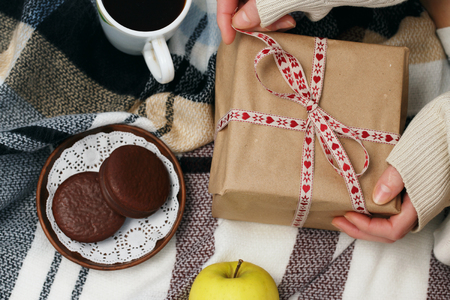 Gift on Valentines Day in the hands of a girl next to coffee, cake and apple