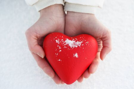Red heart in female hands on a background of snow