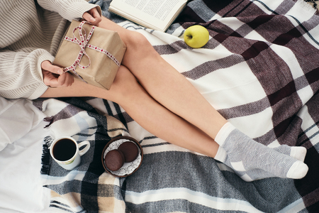 Soft cozy photo of woman in warm sweater on the bed with a gift in their hands, top view point. Girl sitting on checkered plaid near book and coffee