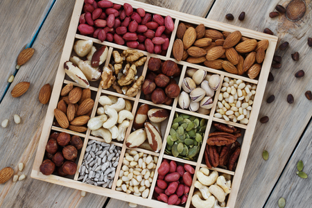 Box of nuts on a wooden table, top view Stock Photo