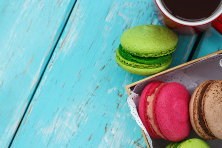 Macaroon cakes in a box and mug of tea with space for text