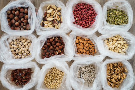 Background of the packages with nuts on a wooden table, top view