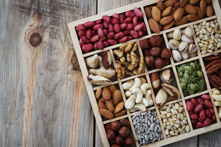 Box of nuts on a wooden table with space for text, top view