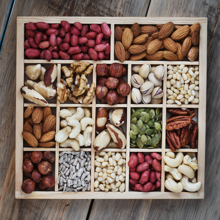 Top view on a box of nuts on a wooden table, close-up
