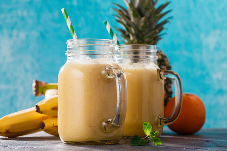Smoothies of pineapple, banana and orange in a glass jar, close-up