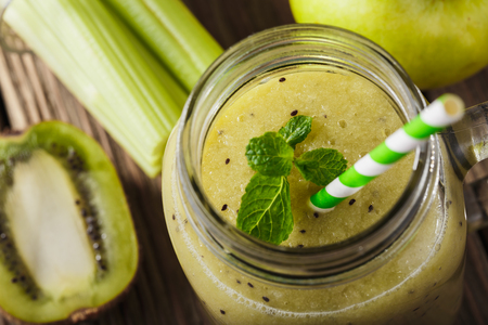 Smoothies of kiwi, celery and apple in a glass jar, close-up