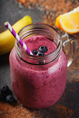 Smoothies of blueberry, banana and orange in a glass jar, close-up Stock Photo