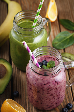 Fruit smoothies in glass jars on a wooden table