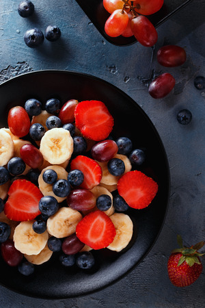 Useful breakfast of fruits and berries, top view. Sliced bananas, strawberries, grapes and blueberries in a black plate
