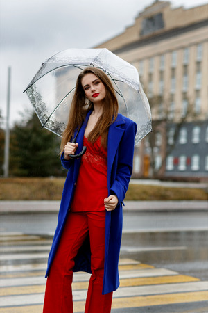 Young beautiful girl posing in fashionable clothes on a city street with an umbrella in hands Stockfoto