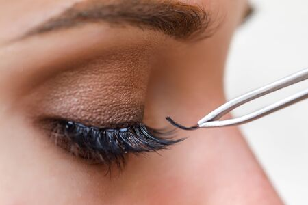 Working process of gluing artificial eyelashes on the eye of the model, macro