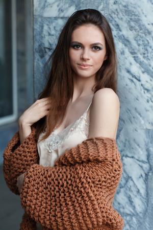 壁の近くのファッショナブルな服の若い美しいブルネットの少女