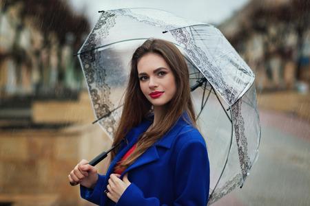 小さな雨から傘の下に隠れて美しい少女の肖像画。モデルのビューがカメラに向けられて