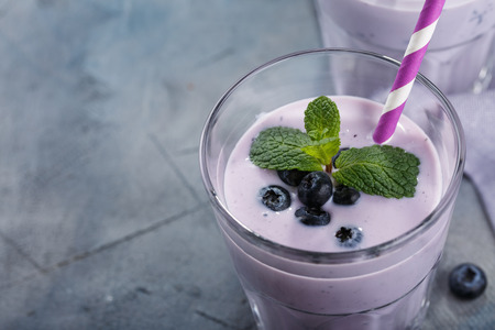 Glass of yogurt with blueberries and mint leaves with space for text, close-up