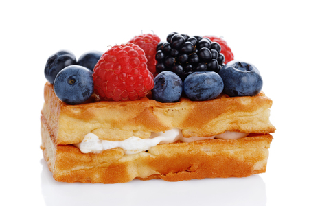 Viennese waffles with fresh blueberries, blackberries and raspberries isolated on white background