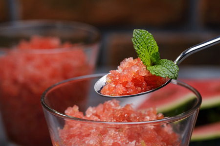 Natural dessert, granite from watermelon and lime in a spoon with mint, closeup.