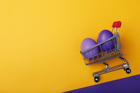 Multicolored easter eggs in a grocery cart with space for text. Holiday ingredients on a yellow background, top view