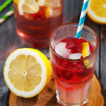 Glass of water with raspberries, slices of lemon and ice Stock Photo