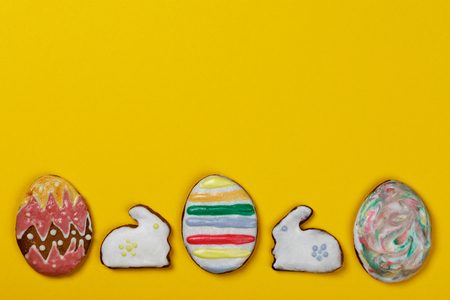 Homemade cookies in the form of Easter eggs and rabbits on a yellow background with space for text, top view Stock Photo