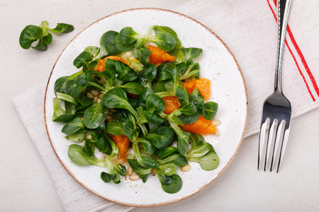 Dietary lunch: gentle salad Korn with pine nuts and tangerine. Dish for vegetarians, top view