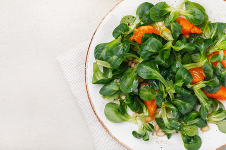 Delicate Korn salad with pine nuts and tangerine. Top view of food with space for text