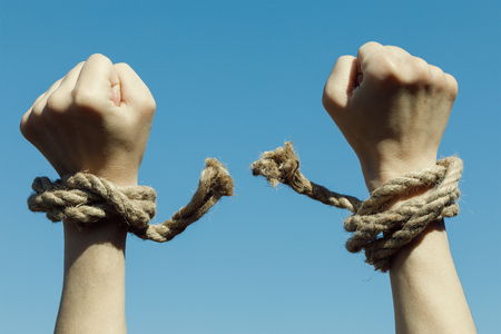 Hands tearing shackles the background of blue sky. Concept of freedom Stockfoto
